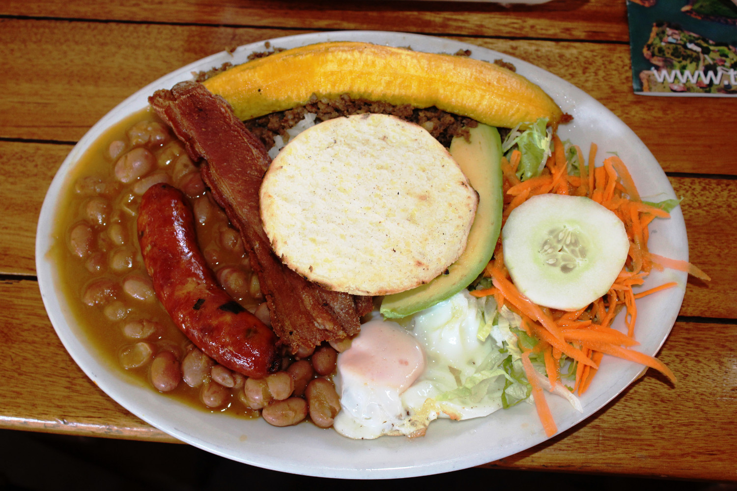 "Fixstarter auf jeder kolumbianischen Speisekarte ist ""Bandeja Paisa"": Knacker, Schweinehaut, Banane, Bohnen, Ei, Avocado 